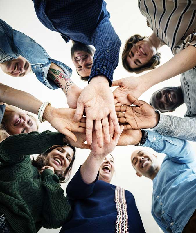 Foto de um grupo de pessoas dando as mãos